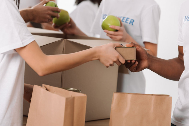 cropped shot of group of volunteers packing food into paper bags